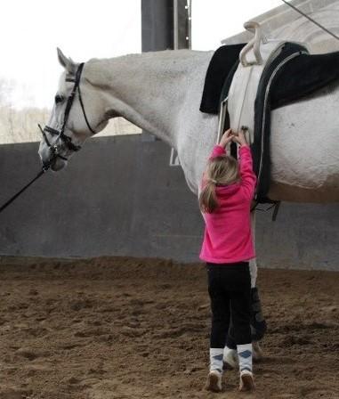 Kind beim Training hält sich am Gurt fest